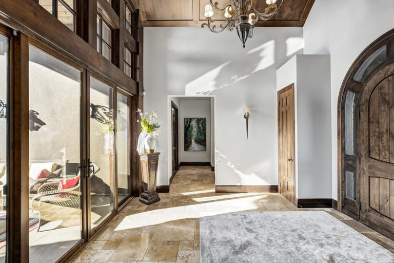 Foyer with arch entry door, chandelier, and glass patio doors.