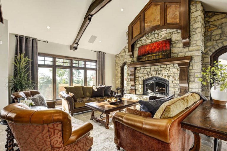 Living room with vaulted ceilings and floor-to-ceiling stone fireplace at 55 Elmont Drive SW. Home sold by Plintz Real Estate.