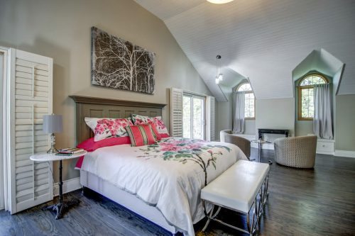 Luxury bedroom with queen bed, floral blanket, vaulted ceilings at 176127 168 Avenue W in Priddis, Alberta, Canada. Acreage home for sale by Plintz Real Estate Calgary.