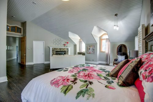 Master bedroom with dormer windows and floral bedspread and fireplace