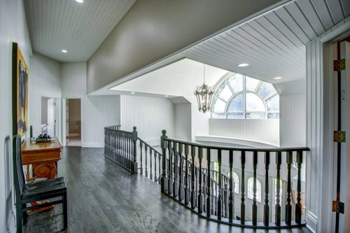 Upper hallway overlooking foyer with arched window and chandelier