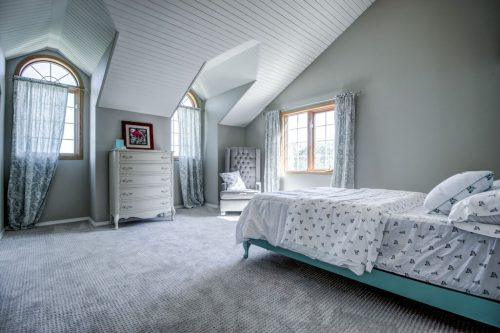 Bedroom with vaulted slatted ceiling and arched dormer windows. Dresser, chair, and bed 176127 168 Avenue W in Priddis, Alberta, Canada. Acreage home for sale by Plintz Real Estate Calgary.