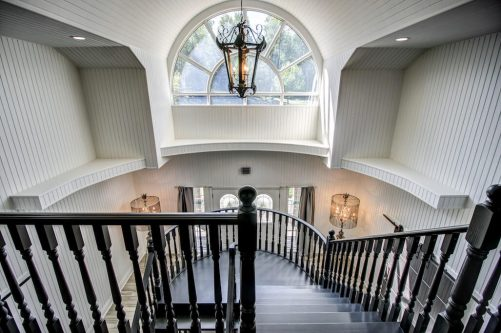 Staircase with chandelier and arched clerestory window wainscotting