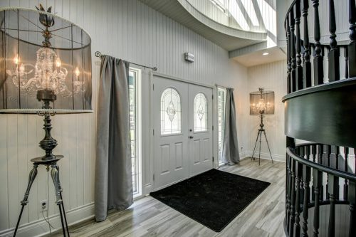 Double entry door into two-storey foyer with spiral staircase at 176127 168 Avenue W Priddis acreage for sale in Alberta. Home for sale by Plintz Real Estate Calgary