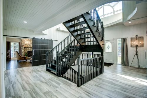 Two-storey foyer entry staircase with hardwood floors 176127 168 Avenue W Priddis acreage for sale in Alberta. Home for sale by Plintz Real Estate Calgary