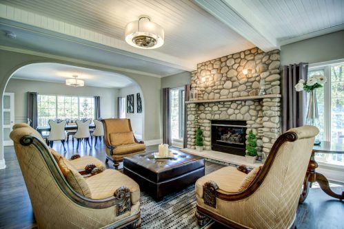Sitting room with river rock stone fireplace open to the formal dining room.