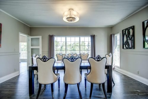 Formal dining room with fancy dining chairs and wood slatted ceiling 176127 168 Avenue W Priddis acreage for sale in Alberta. Home for sale by Plintz Real Estate Calgary