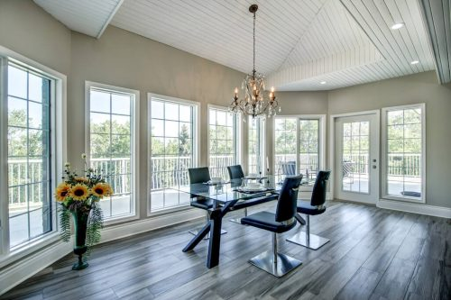 Breakfast nook with floor to ceiling windows and wood slat ceiling and chandelier 176127 168 Avenue W Priddis acreage for sale in Alberta. Home for sale by Plintz Real Estate Calgary