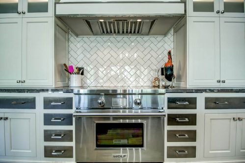 Wolf induction stove with industrial range and white cabinetry