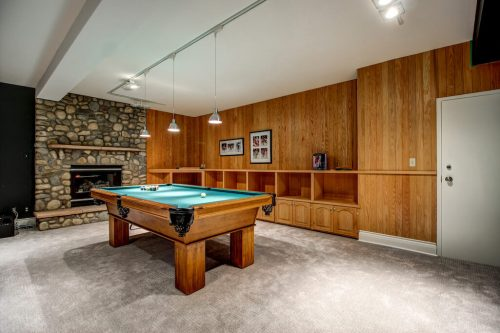 Basement with pool table and stone fireplace and custom built ins 176127 168 Avenue W Priddis acreage for sale in Alberta. Home for sale by Plintz Real Estate Calgary