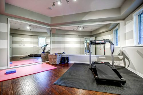 Fitness room gym with mirrors, treadmill, and yoga mat