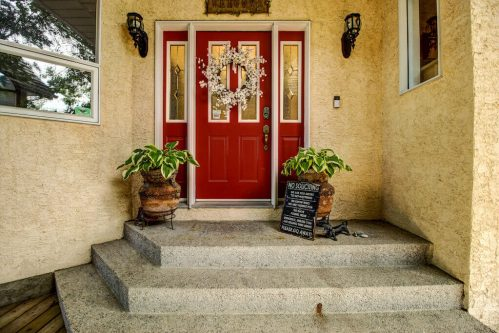 Red door entrance of 587 East Chestermere Drive Alberta. Home for sale by Plintz Real Estate Calgary.