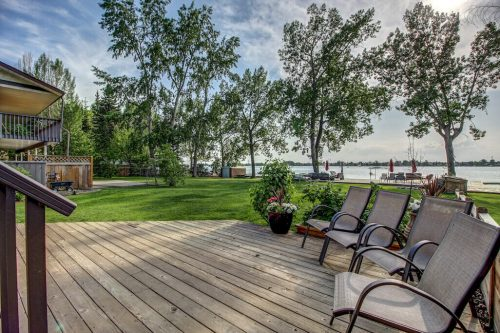 Back deck with patio chairs overlooking backyard in summer and dock into Chestermere Lake.