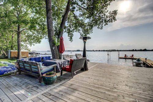 Private deck with patio furniture on Lake Chestermere at 587 East Chestermere Drive Alberta. Home for sale by Plintz Real Estate Calgary.
