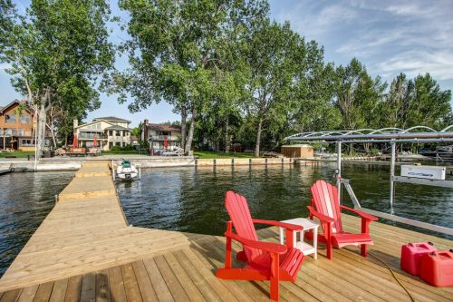 Private dock on lakefront home red andronack chairs
