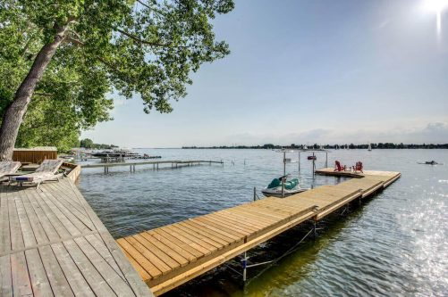 Lakefront home with private dock on a beautiful summer day at 587 East Chestermere Drive Alberta. Home for sale by Plintz Real Estate Calgary.