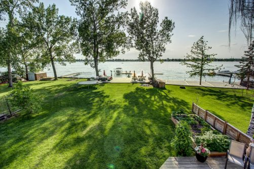 View of backyard lawn and private dock on Chestermere Lake in the summer.