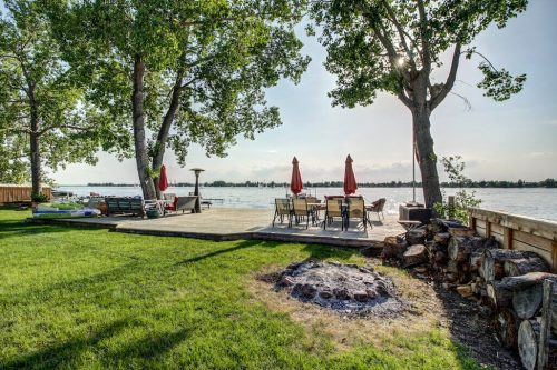 Firepit and dock with dining table at lakefront.