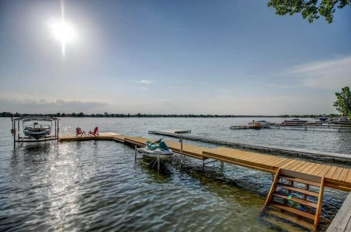 Boat launch and seadoo on Chestermere Lake private dock at 587 East Chestermere Drive Alberta. Home for sale by Plintz Real Estate Calgary.