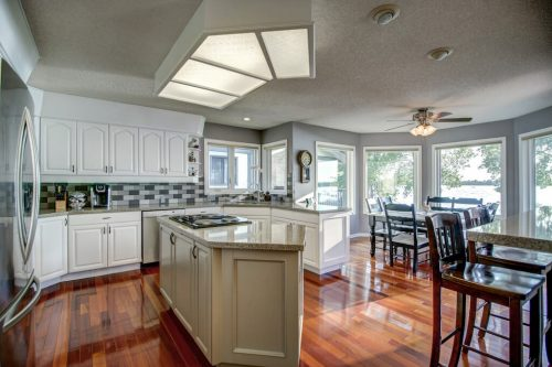 Kitchen with white cabinetry and centre island with view of lake.