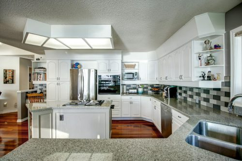 Kitchen with white cabinetry and checkered backsplash and granite countertops.