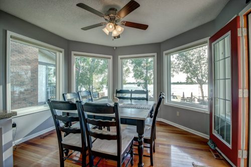 Breakfast nook with ceiling fans and windows with view of Chestermere Lake.
