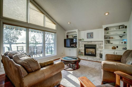 Living room with vaulted ceilings, fireplace, and floor-to-ceiling windows with views of Chestermere Lake.