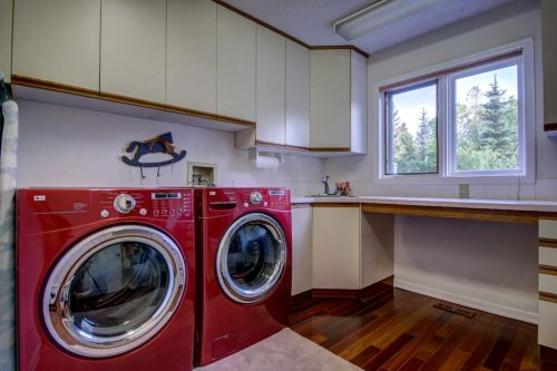 Laundry room with red front loading washer and dryer.