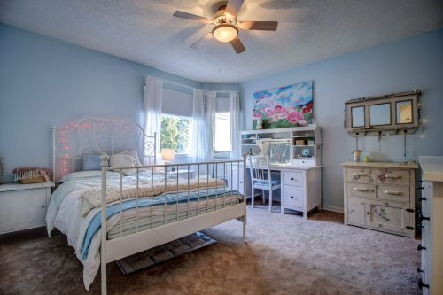 Children's bedroom with white bed and desk.