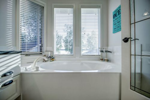 Corner soaker tub with views of Chestermere Lake.