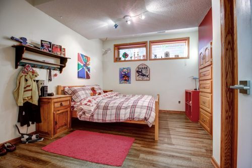 Child bedroom with wood bed, dresser, and night stand.