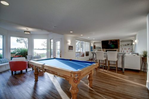Pool table in games room in walkout basement at 587 East Chestermere Drive Alberta. Home for sale by Plintz Real Estate Calgary..