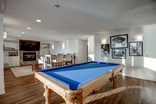 Pool table in games room in walkout basement in 587 East Chestermere Drive Alberta. Home for sale by Plintz Real Estate Calgary.