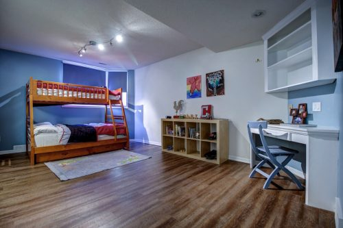 Boy's bedroom with blue accent wall, bunkbeds, and white desk.