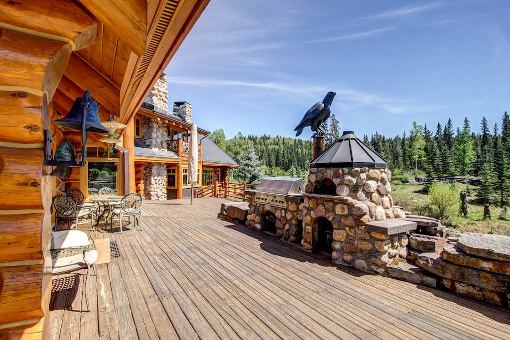 Deck-stone-outdoor-fireplace-views-nature-realtor-352248-Pine-Ridge-Road-Bragg-Creek-Ranch-Acreage-For-Sale-Calgary-Real-Estate-For-Sale-taylor-sothebys-pond