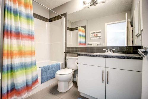 Bathroom with rainbow shower curtain in NW Calgary home for sale by Plintz Real Estate.