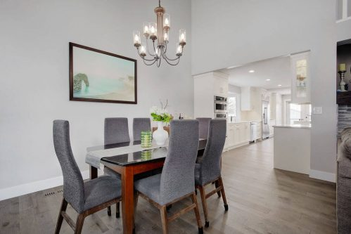 Dining room with grey chairs and chandelier in Calgary home for sale by Plintz Real Estate.
