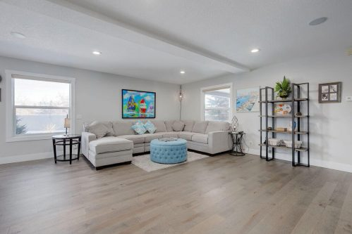 Living room with corner sectional and baby blue ottoman.