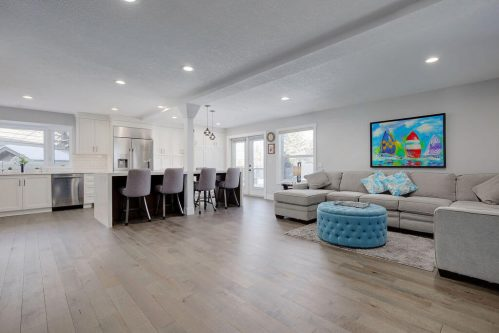 Large open layout with hardwood floors and large kitchen island with grey stools.
