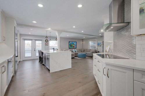 Open concept living space with white kitchen and large marble island in Lake Bonavista home for sale by Plintz Real Estate.