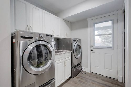 Laundry with front loading stainless steel washer and dryer in mudroom of Lake Bonavista home in Calgary.