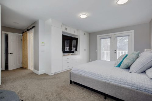 Master bedroom with french doors to patio and built-in entertainment unit.