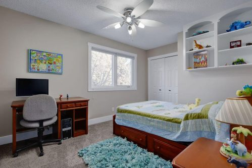 Children's bedroom with dinosaur decor in Calgary home for sale by Plintz Real Estate.