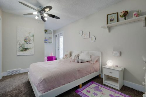 Girls bedroom with ceiling fan in Calgary home for sale by Plintz Real Estate.