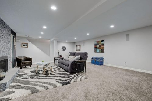 Basement with high ceilings and stone fireplace in Lake Bonavista home in Calgary.