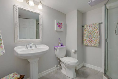 Three piece bathroom with pedestal sink, toilet and shower in Calgary home.