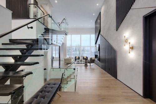 Open riser staircase in ultra modern luxury home with hall flowing to the great room with floor to ceiling windows.