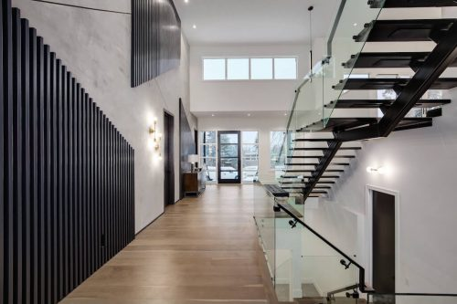 Monochrome interior design in modern luxury home with open riser staircase.