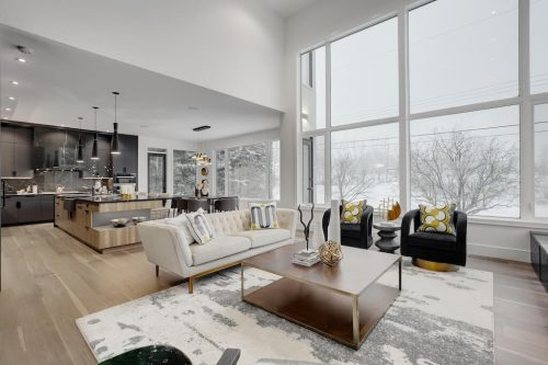 Great room with high ceilings and large windows overlooking snowy backyard and bow River in Calgary.