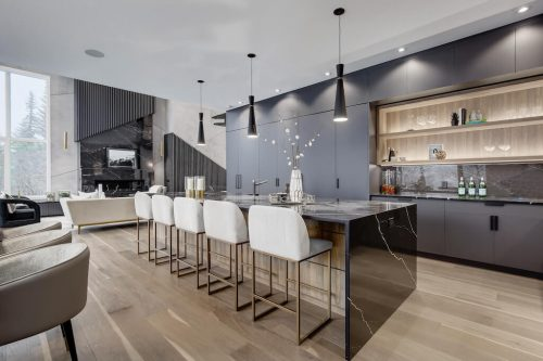 Modern design in luxury home with large marble island, black cabinetry, and abstract fireplace in Scarboro Calgary home for sale by Plintz Real Estate.